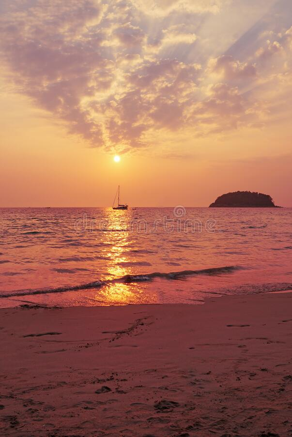 Dawn over the sea and a small sailing boat royalty free stock photo