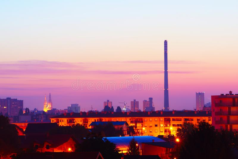 Dawn Over Zagreb Suburbs. View on Zagreb suburbs ?pansko and Rude? with apartment blocks, houses, greenhouse and cathedral towers and power station chimney in royalty free stock image