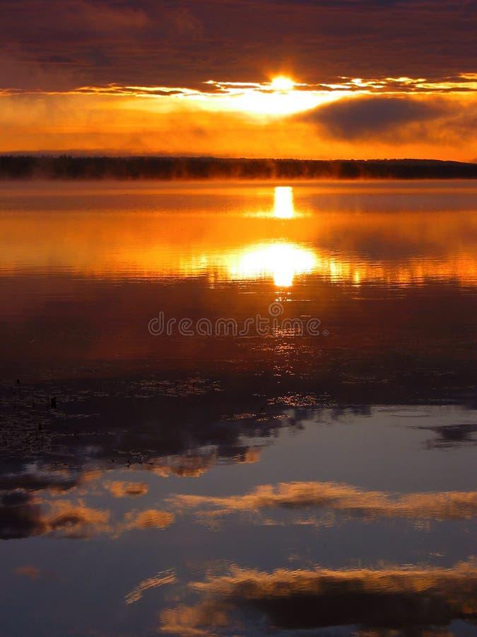Dawn Reflections. A bright sunrise on Fawcett Lake, Alberta, Canada stock image