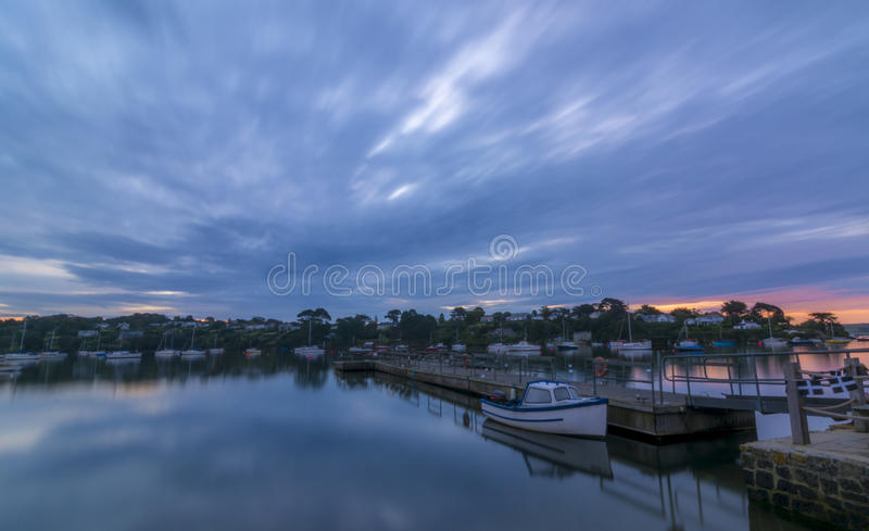 Dawn on the river Fal in Cornwall, England. Long exposure, with a boat moored in the forefront of the frame stock image