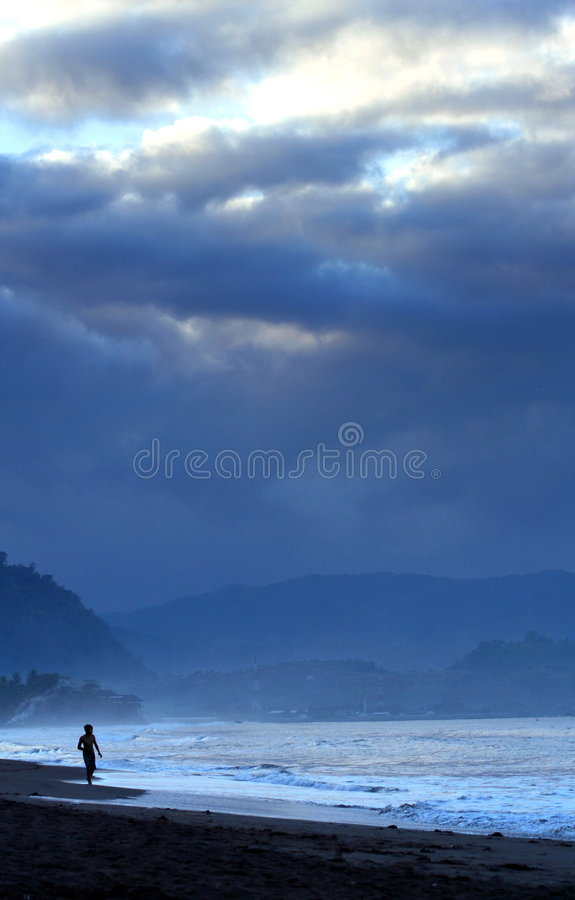 Dawn Runner. A picture of a man running at beach limit. Taken at Pelabuhan Ratu Beach, Indonesia royalty free stock images