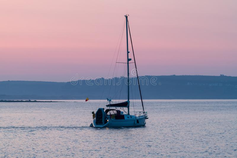 Dawn Sailing from Porthcawl Harbour. A yacht leaves Porthcawl  harbour on the early morning tide stock photo