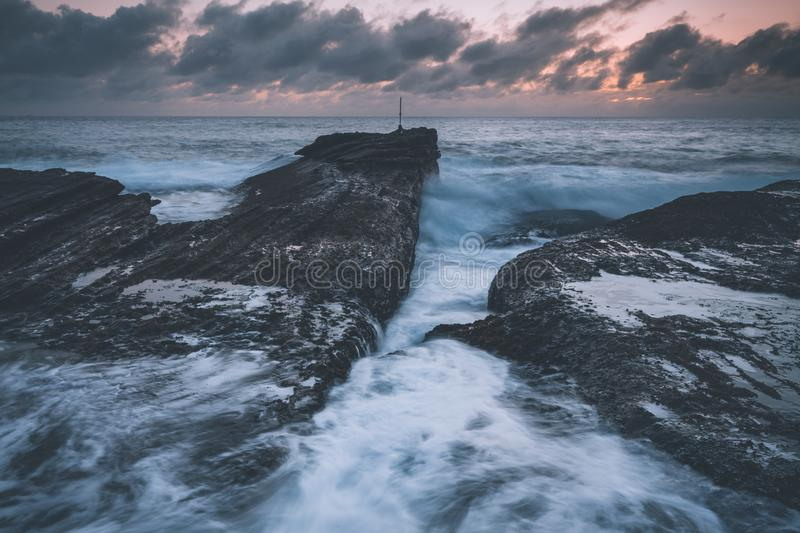 Dawn Skies, Moody Seas and Rocky Chasms Landscapes. Dawn skies with a pre sunrise glow behind heavy grey clouds. Moody seas surge forth waves that batter the royalty free stock photo