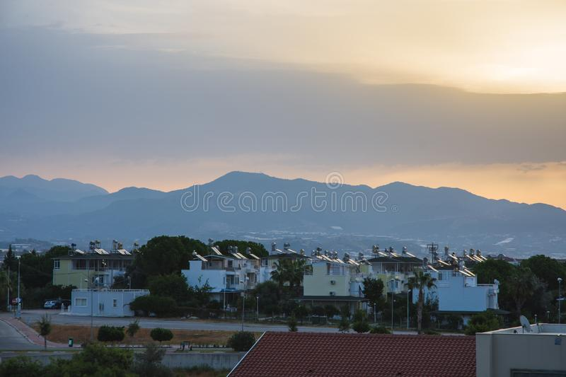 Dawn in summer over the city in the mountains with hanging clouds on the horizon at sea. Turkey, Alanya. royalty free stock images