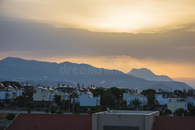 Dawn in summer over the city in the mountains with hanging clouds on the horizon at sea. Turkey, Alanya. stock image