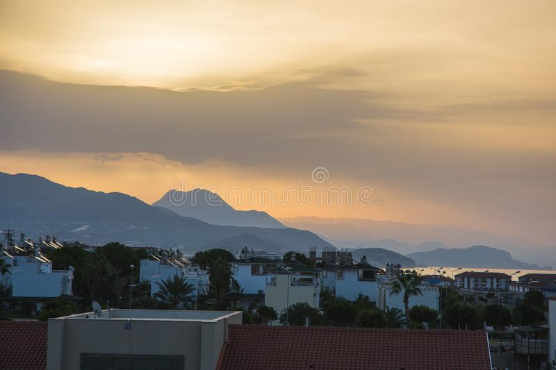 Dawn in summer over the city in the mountains with hanging clouds on the horizon at sea. Turkey, Alanya. stock photo