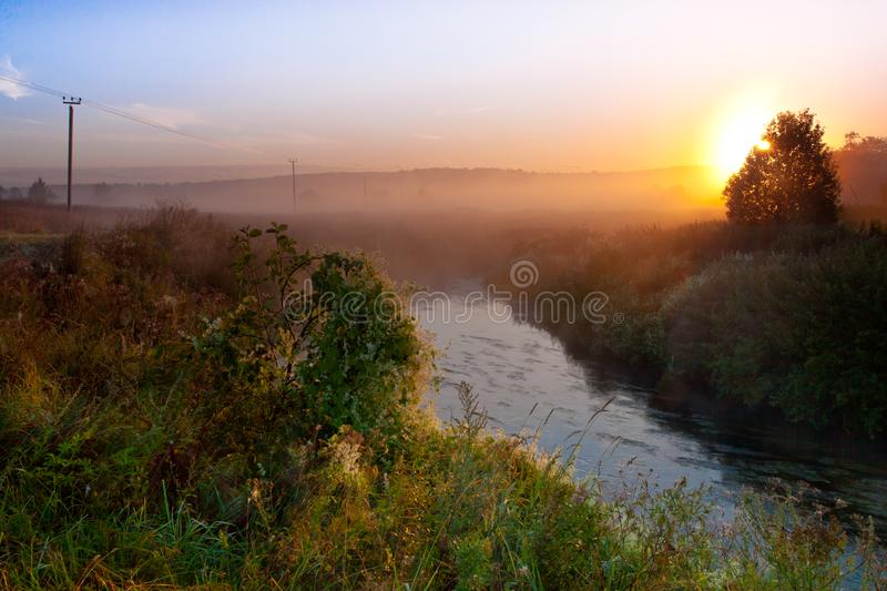 Dawn the sun rises over the river and rural landscape, fog royalty free stock images