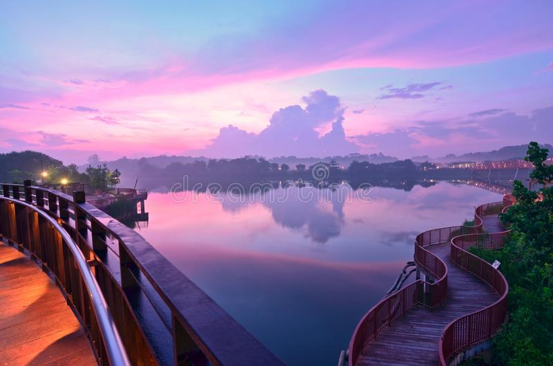 Dawn Winding Path. Misty dawn landscape overlooking Serangoon Reservoir. Winding path boardwark on the right and curved lines of the Sunrise Bridge on the left stock photography