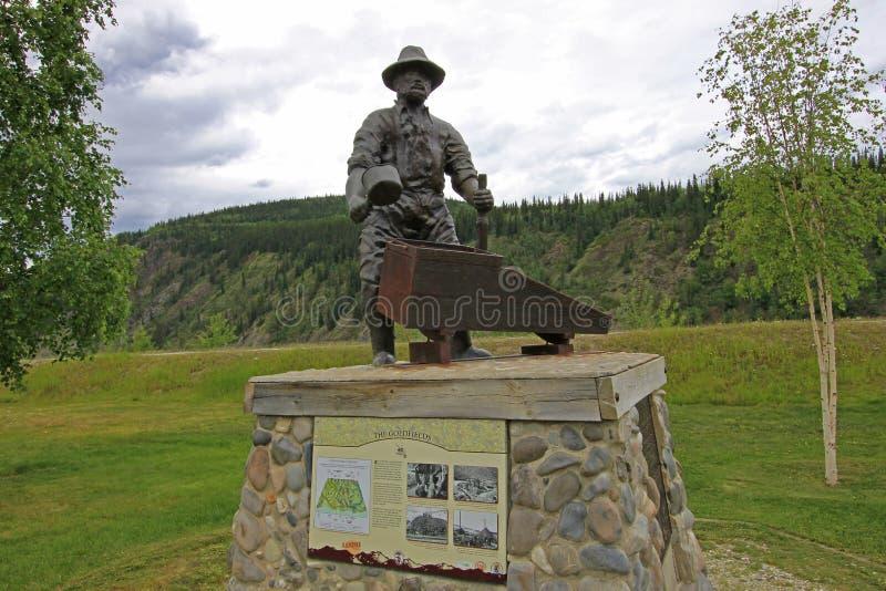 DAWSON STAD, YUKON, KANADA, JUNI 24 2014: Monumentet av gruvarbetaren George Washington Carmack i Dawson City, Kanada på Juni arkivbilder