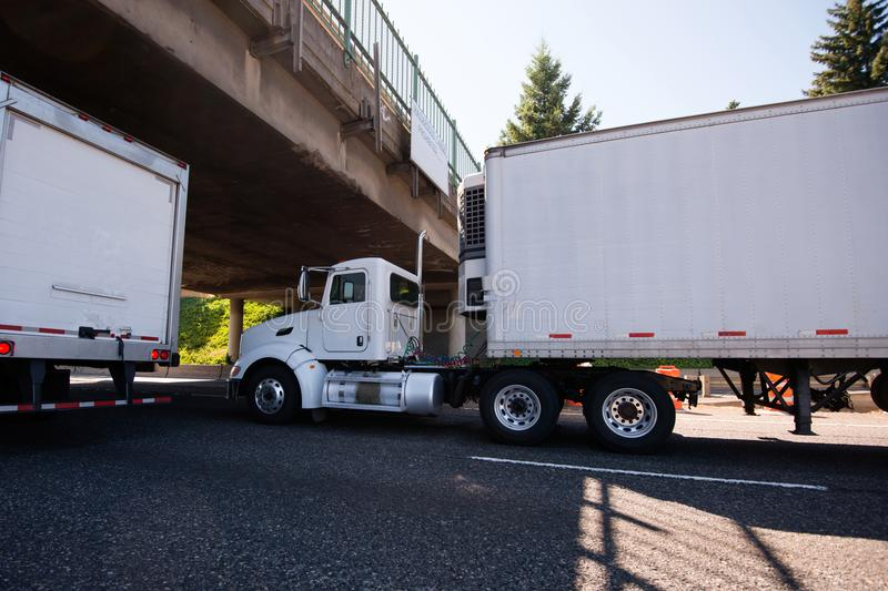 Day cab big rig semi truck going with reefer trailer with refrigeration unit under the bridge on roadside with traffic. Day cab white big rig semi truck with stock image