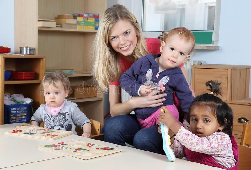 Day care or kindergarten kids and teacher playing with a puzzle stock images