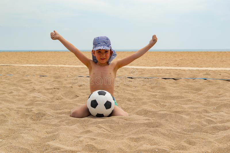 During the day the child plays football on the beach. stock image