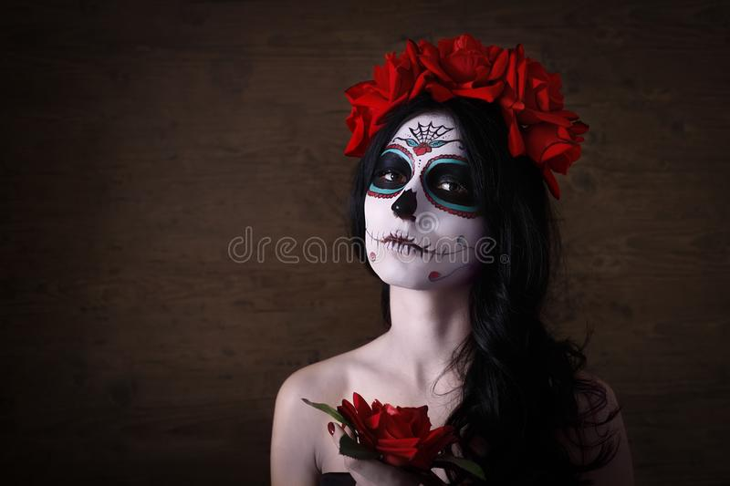Day of the dead. Halloween. Young woman in day of the dead mask skull face art and rose. Dark background. stock photos