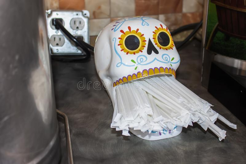 Day of the Dead straw dispenser on counter with plastic paper wrapped straws in mouth opening stock photo