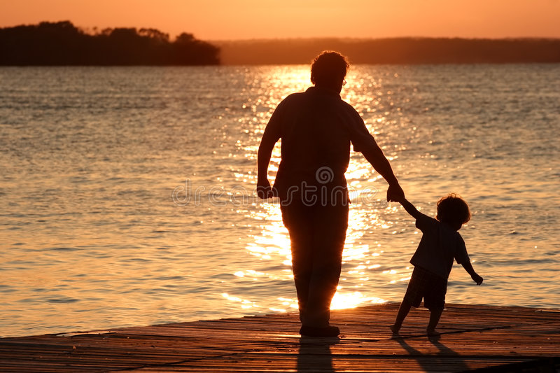 Day is Done. An adult and a child walk out on a dock as the sun sets