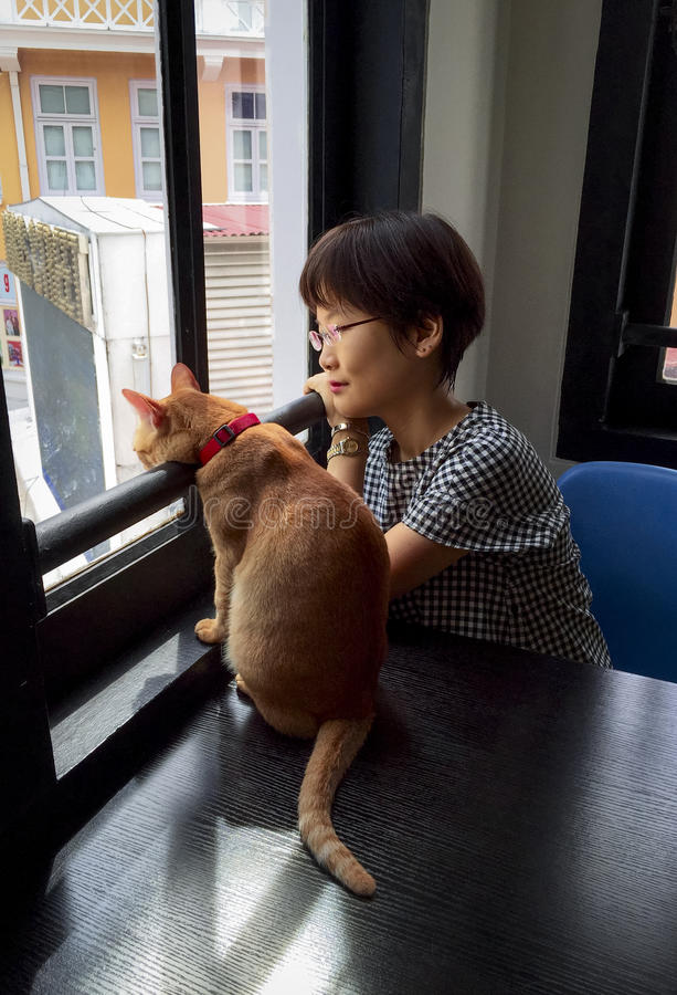 Day Dreaming. Asian girl with cat looking outside the glass window