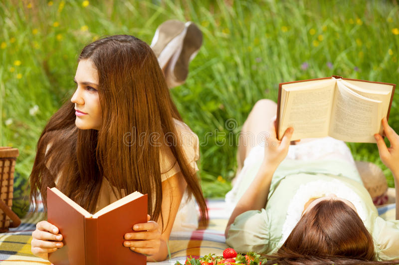 Day dreaming. Two girls are resting in park with books royalty free stock image