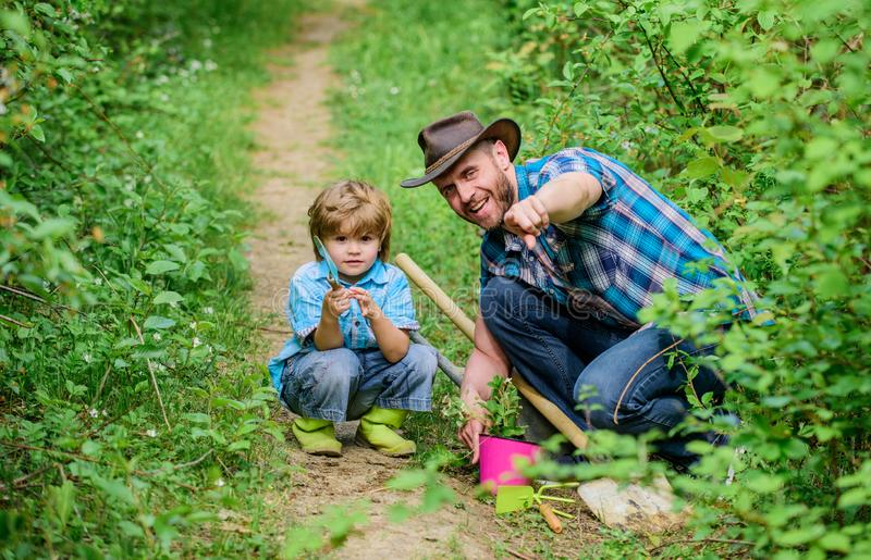 Day of earth. Boy and father in nature. Gardening tools. Planting flowers. Dad teaching little son care plants. Little. Helper in garden. Make planet greener royalty free stock image