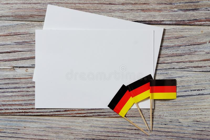 October 3 happy Day of German unity. the concept of patriotism , freedom and independence. Mini flags with a white card on wooden. Day of German Unity written in stock photos
