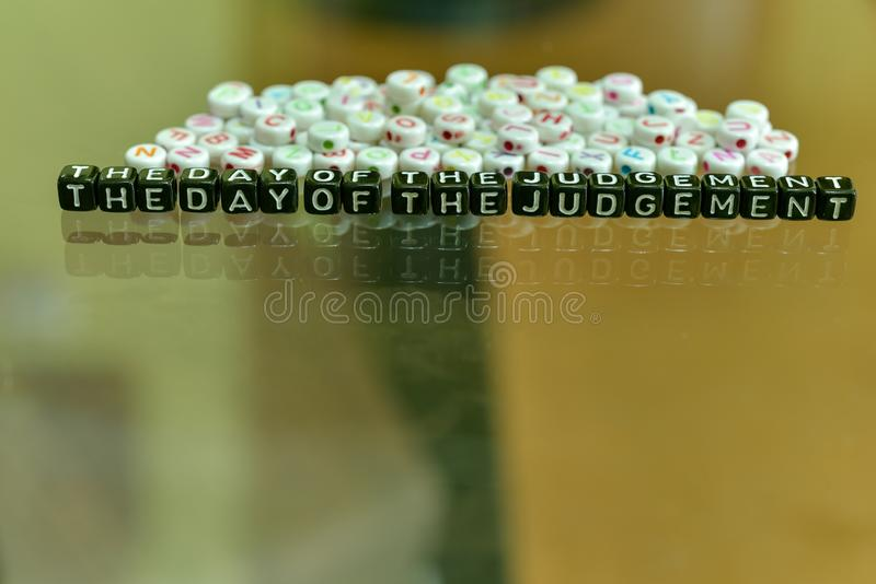 THE DAY OF THE JUDGEMENT  written with Acrylic Black cube with white Alphabet Beads on the Glass Background.  stock photography