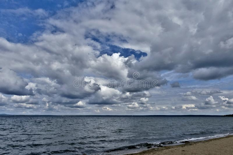 Day lake in gray-white cloudy weather. South Ural, Uvildy, in the distance are seen the Ural mountains stock image