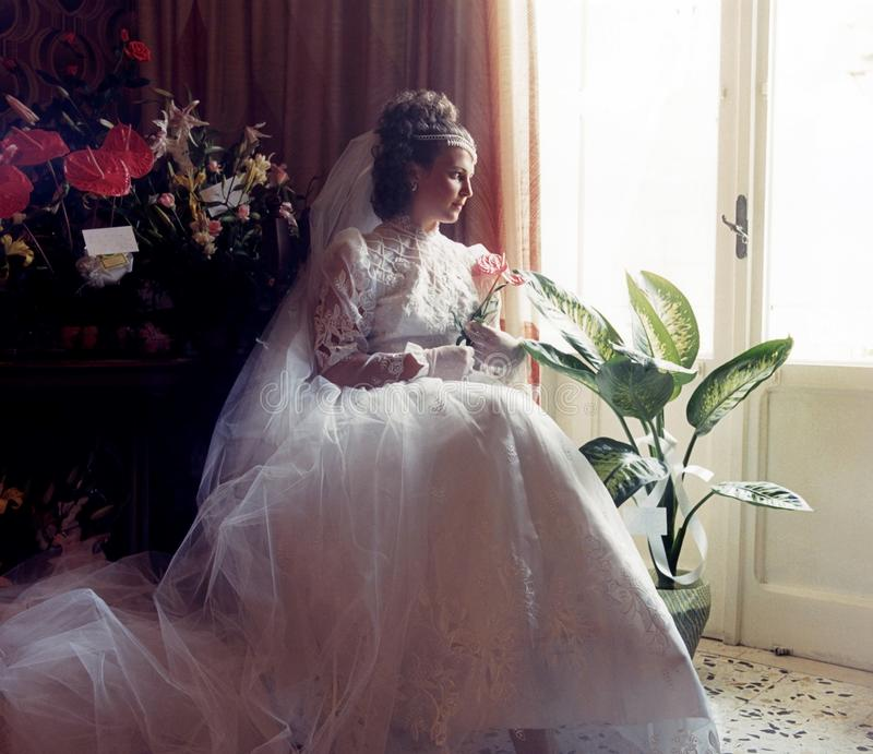 The day of the marriage. Beautiful young bride in a stylish wedding dress and posing at her home before the wedding celebration stock photos