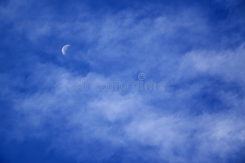Day moon with clouds stock photography