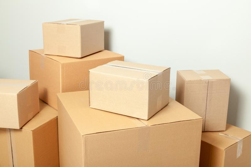 Day moving. Delivery of goods, shopping. Cardboard boxes on gray wall background.  royalty free stock image