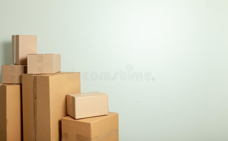 Day moving. Delivery of goods, shopping. Cardboard boxes on gray wall background. Copy space for text. Day moving. Delivery of goods, shopping. Cardboard boxes royalty free stock images