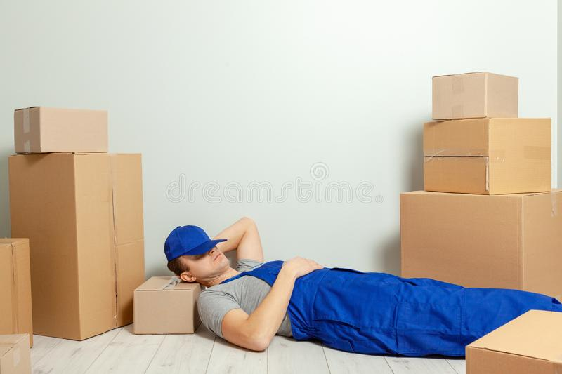 Day moving. Delivery of goods from shopping in the online store. The loader or courier has break and sleeps in the workplace royalty free stock photos