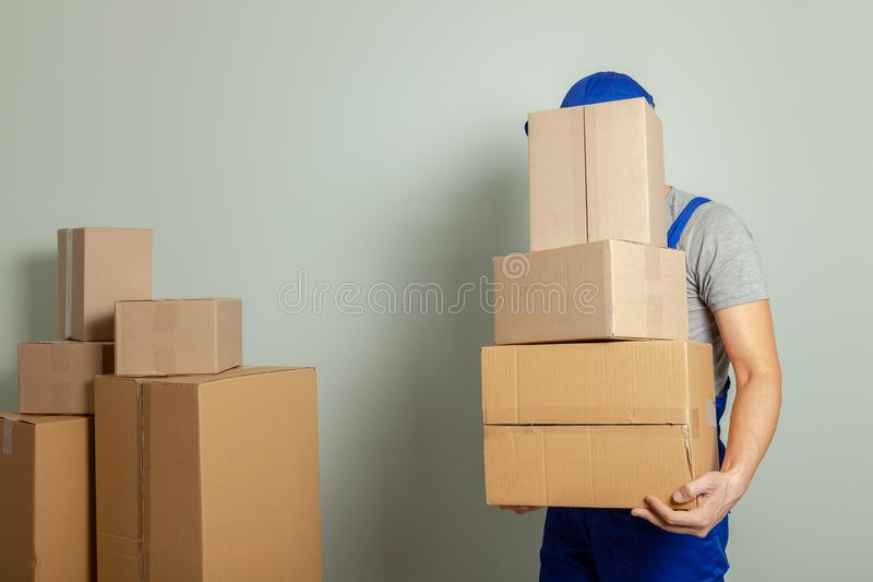 Day moving. Delivery of goods from shopping in the online store. Loader or courier transports cardboard boxes against gray wall.  royalty free stock photos