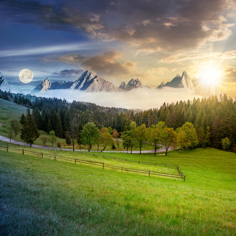 Day and night above rocky peaks behind the forest and meadow royalty free stock image