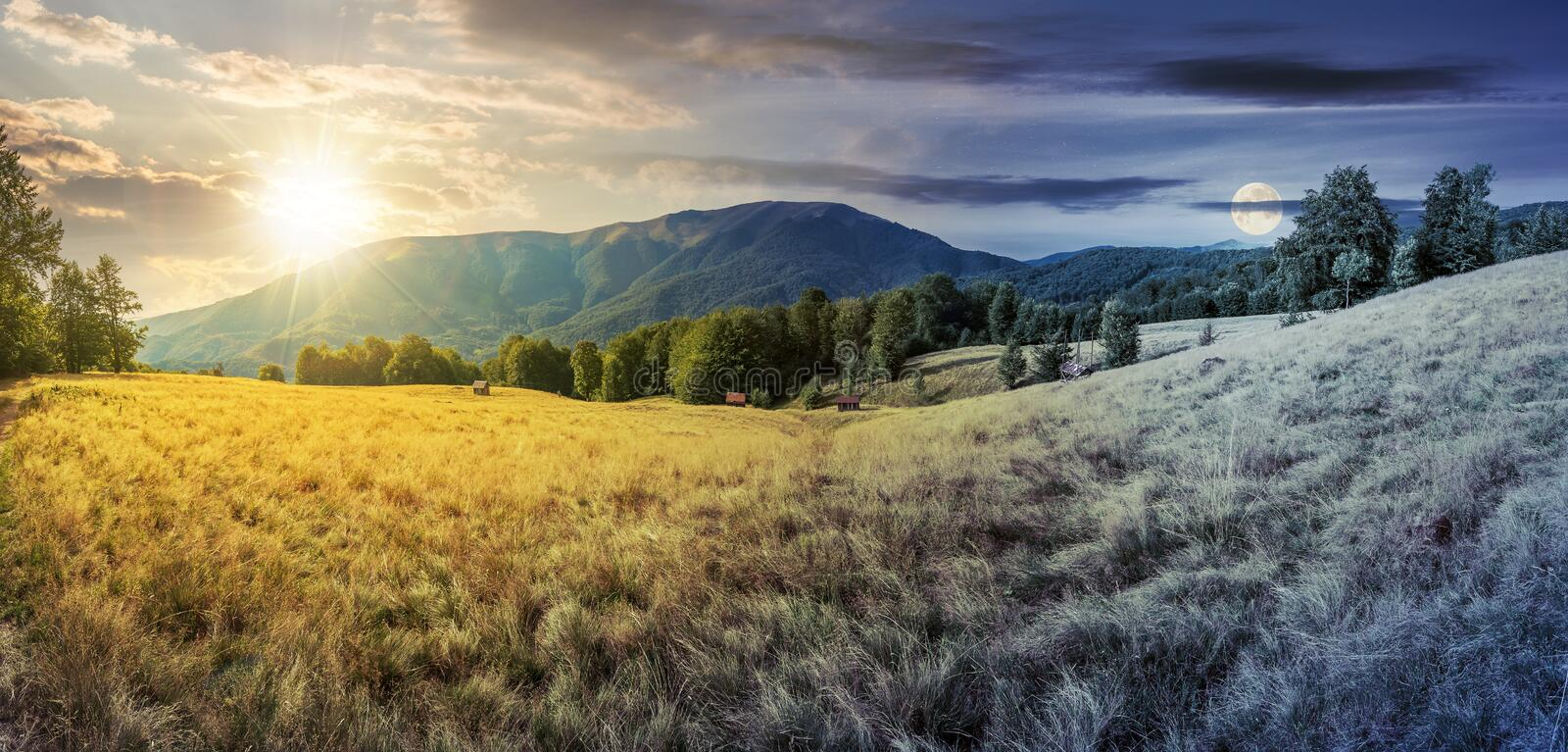 Day and night time change in mountains. Panorama with beech trees on the grassy meadow. ridge in the distance beneath a sky with sun and moon royalty free stock photography