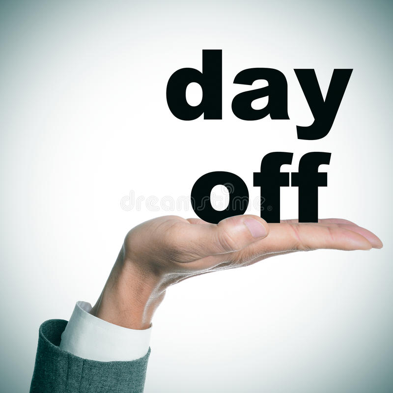 Day off. The hand of a man wearing a suit holding the text day off royalty free stock photography