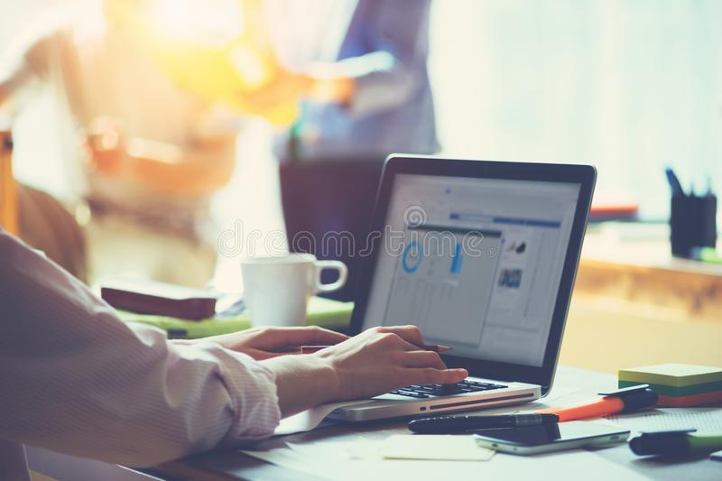 Day in office. Laptop and paperwork on the table. Team brainstorming idea and manager working with project on laptop royalty free stock image