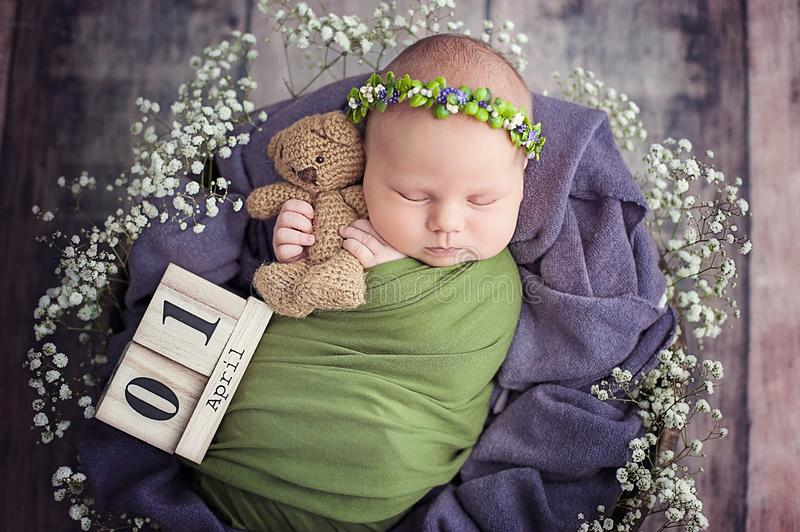 Beginning of life and happy fairy magic childhood concept. 10 day old Smiling newborn baby is sleeping on yellow fur background. 10 day old newborn baby is royalty free stock images