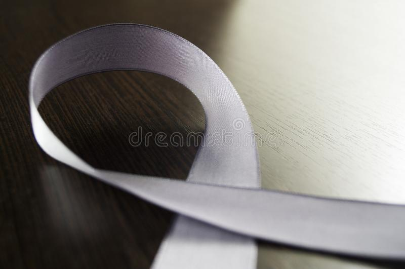 Day of Parkinson. A silver ribbon as a symbol on a dark background. Image stock photos