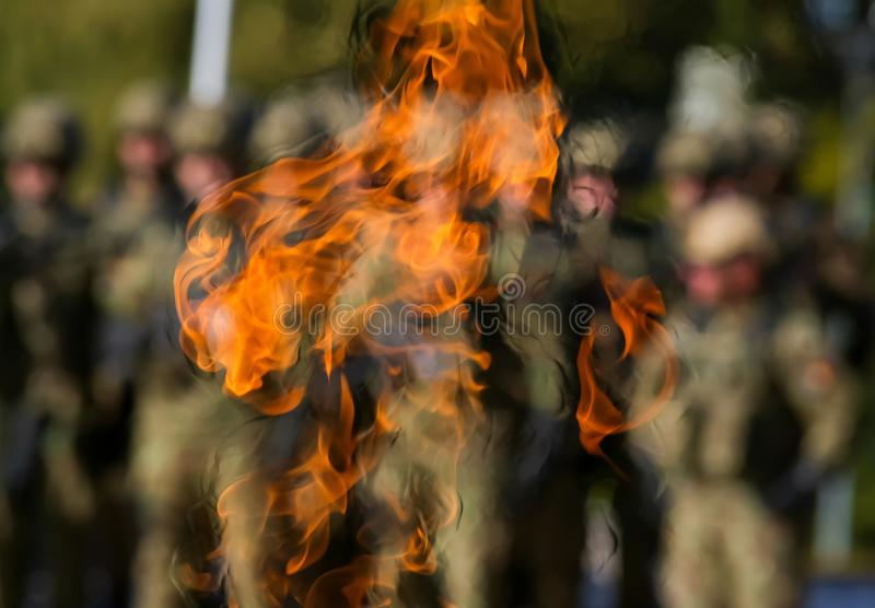 The day of the Romanian army. Bucharest, Romania - October 25, 2018: The elite troops of the Romanian army infantry are seen through the eternal flame that burns stock photos