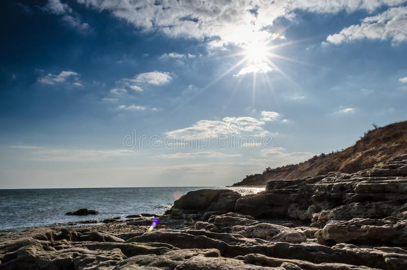 Day seascape with rocks washed by the sea and sun flare royalty free stock image