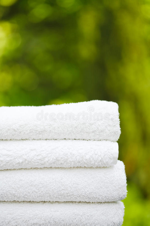 Day spa. Stack of fresh white towels in a garden setting with copyspace, ideal for depicting a day spa or wellness royalty free stock photography