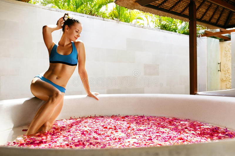 Day Spa Body Care. Woman Relaxing Near Flower Bath Outdoors. Day Spa Body Care. Beautiful Happy Woman With Healthy Skin In Bikini Relaxing Near Round Outdoor stock photography