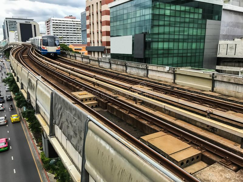 Day view of Electric Sky Train running on the rail tracks in downtown Bangkok, Thailand with ground traffic and tall buildings. In the background stock image