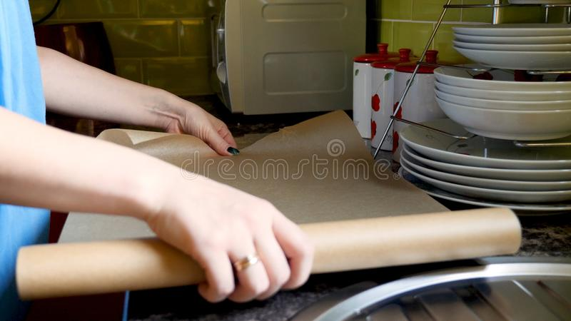 Day view female hands placing baking paper on oven tray tin.  royalty free stock images