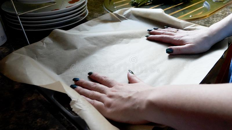 Day view female hands placing baking paper on oven tray tin.  stock photography