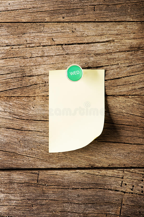 Day of week Sticky note with pin over. Wooden background stock image