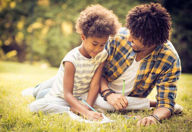 Day for writing. African American father and daughter writing together in nature stock images