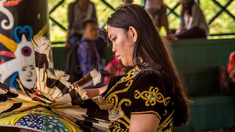 Dayak dancer preparation before perform. Dayak woman dancer with traditional costumes check the hat that full of bird feather before her performance in Erau