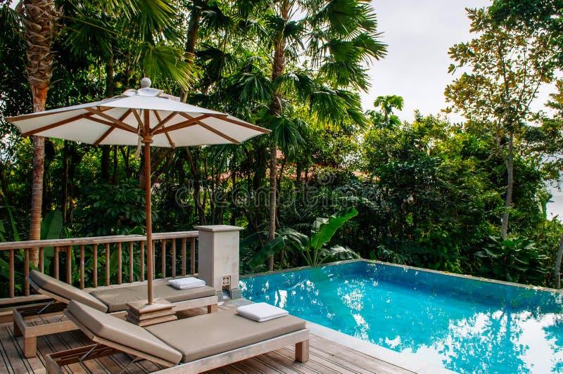 Daybed de station de vacances de relaxation de vacances par la piscine d'infini dans le tropique photo libre de droits