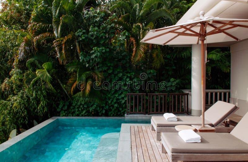 Daybed de station de vacances de relaxation de vacances par la piscine d'infini dans le tropique image stock