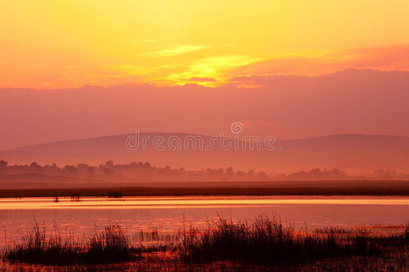 Daybreak. On an autumn daybreak, the colorful sun lights dyed the sky, clouds and the marsh. This is a beautiful seasonal picture stock images